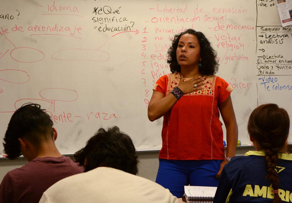 Elizabeth Villanueva stands in front of the classroom.